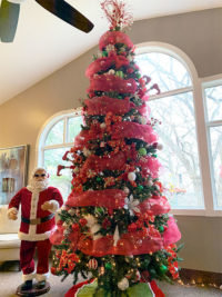 Large Christmas tree in front of window with red ribbon and Santa
