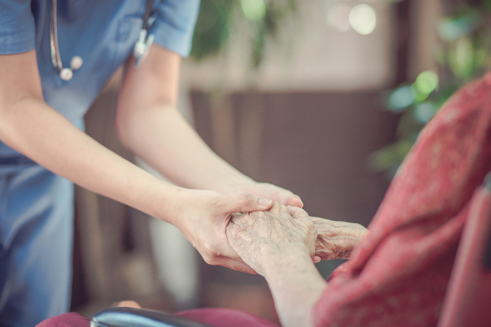 senior holding hands with nurse