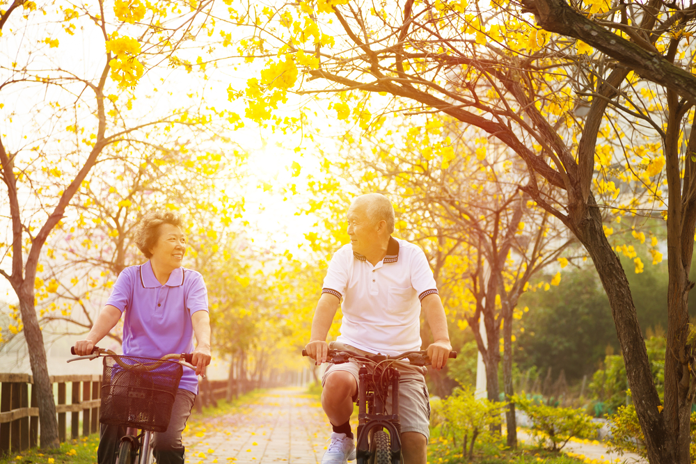 assisted living health and sunlight senior couple riding bikes