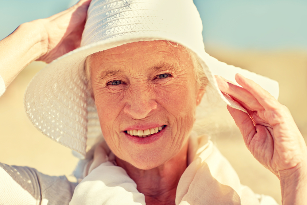 senior woman happy outside with sunhat