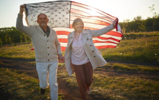 assisted living July holiday senior couple with American flag outside