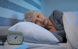 Oakleigh Macomb senior woman looking at clock in bed can't sleep