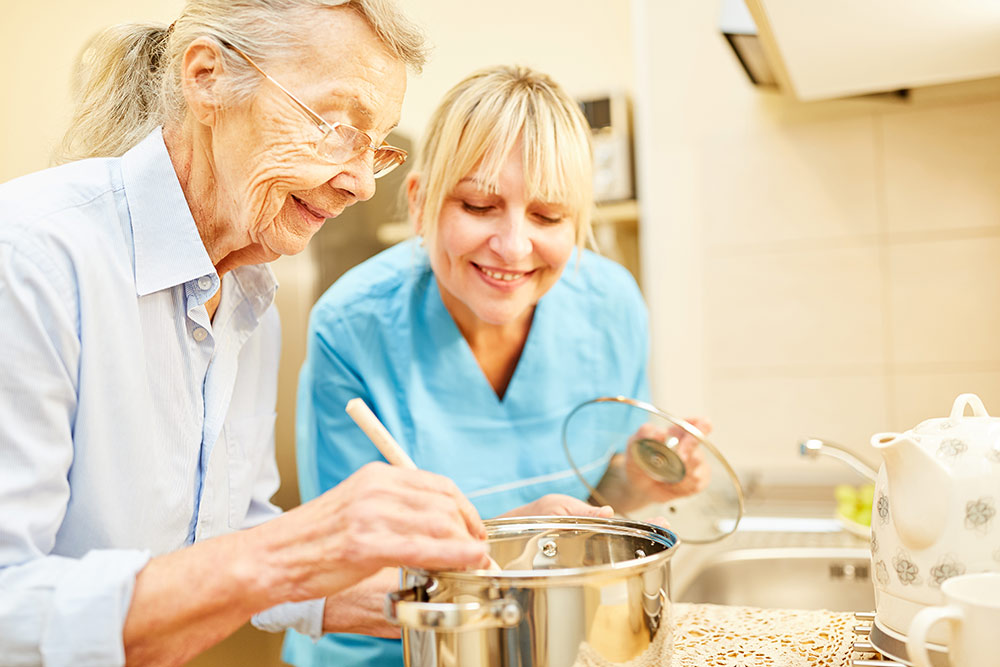 Oakleigh of Macomb Senior Living senior woman with caregiver cooking
