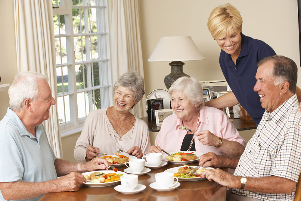 Happy smiling senior group eating meal at table with caregiver near by