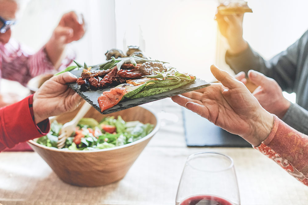 Hands passing plate of health grilled vegetables