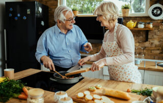 Happy senior couple smiling and cooking in kitchen