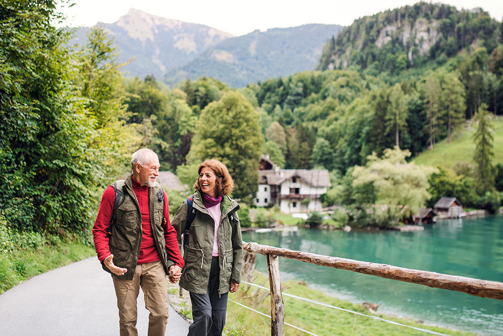 Senior couple walking near lake outside with lake house seen in the background