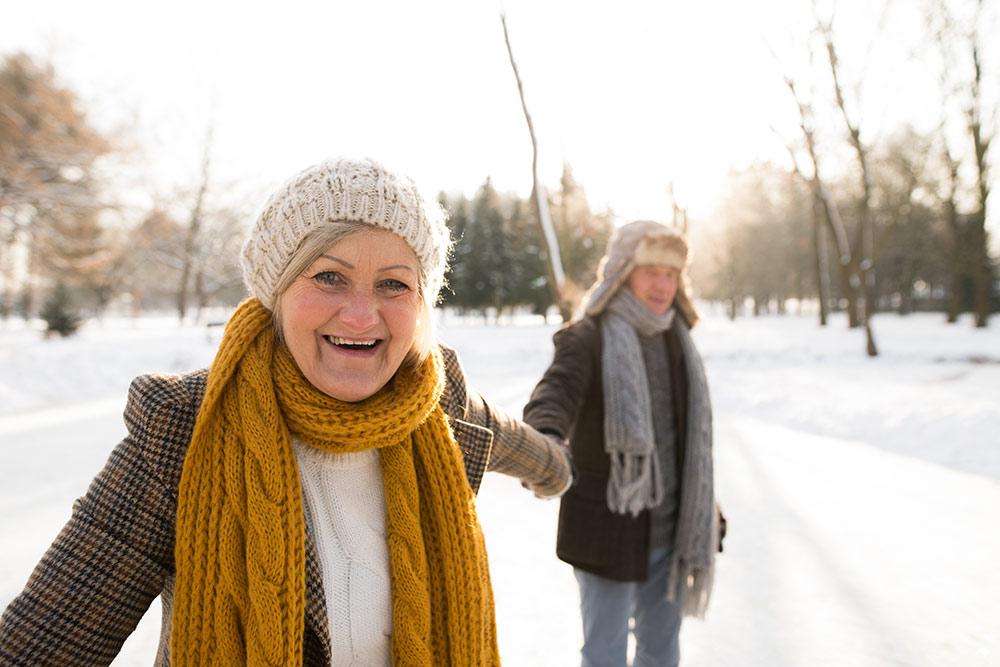 Happy senior couple outside in snow