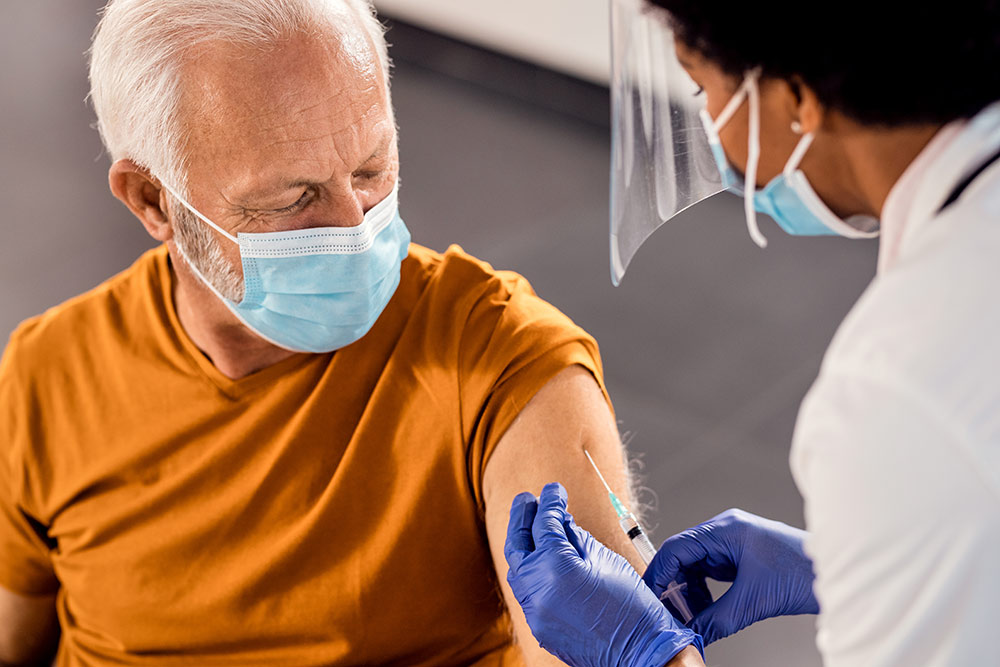 Senior man and doctor, both wear masks, man receiving vaccine from doctor