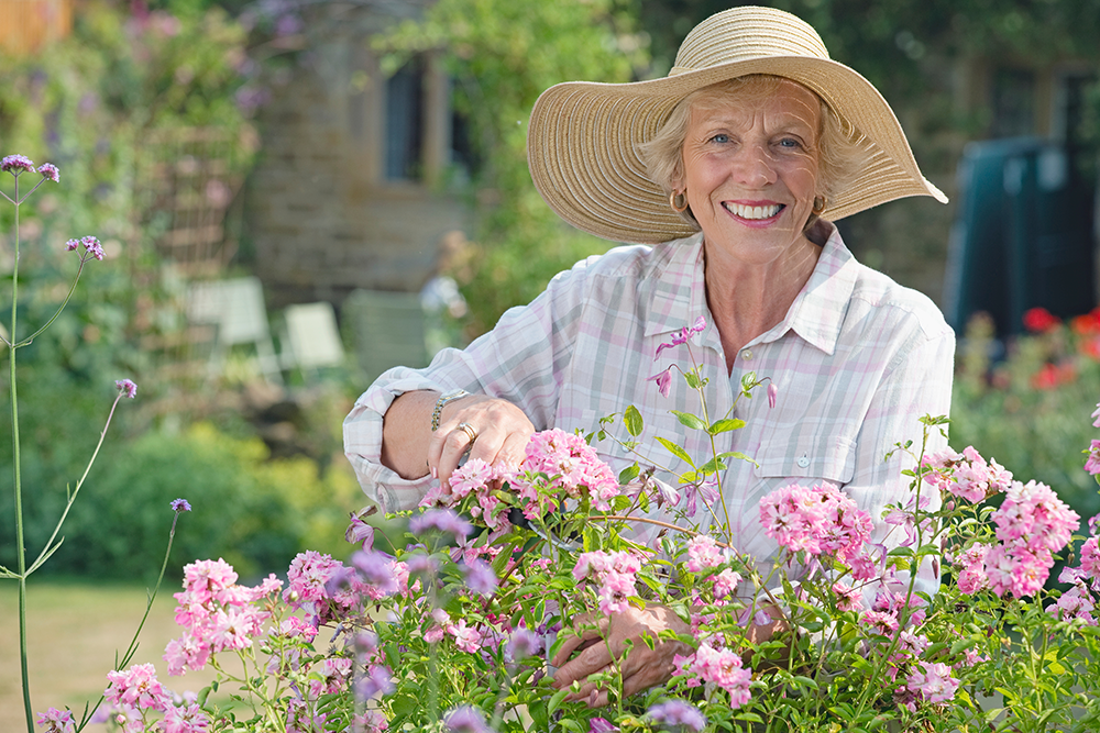 Senior woman smiling and gardening outside in memory care community