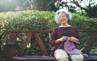Senior woman sitting on bench outside knitting at memory care community