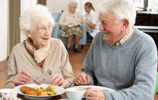 Senior couple eating at table in senior living community