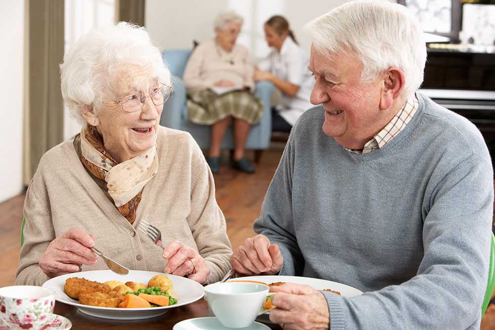 Senior couple eating at table in senior living community