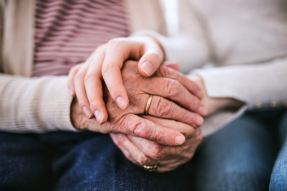 Caregiver and senior holding hands
