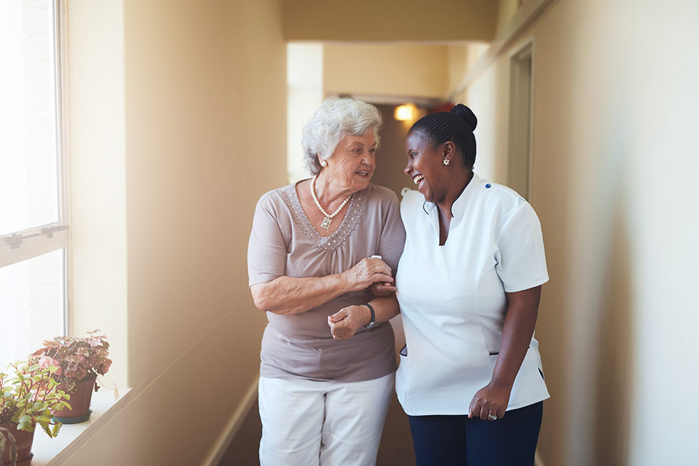 Senior woman walking with caregiver in dementia assisted living facility