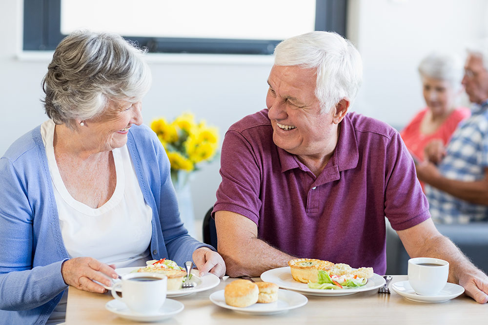 Senior couple eating breakfast at table in senior housing community