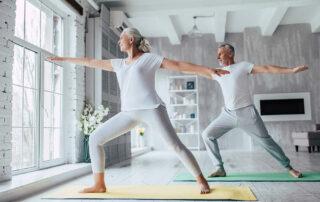 Senior couple doing yoga in living room near window