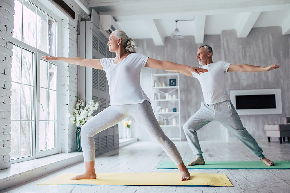 Senior couple doing yoga in living room near window