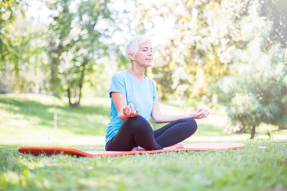 Senior woman meditating outside in grass