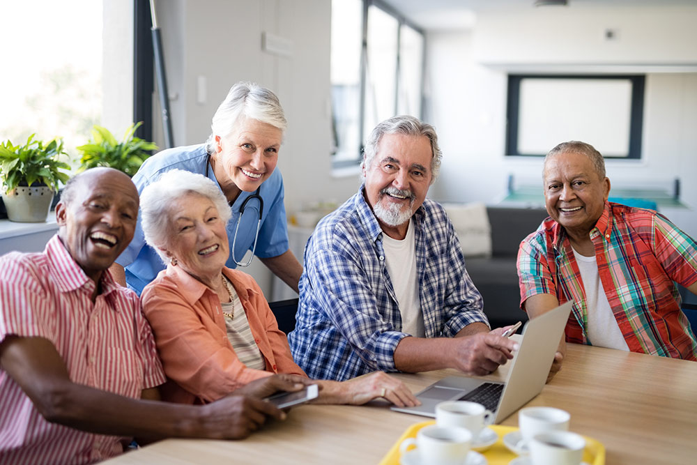 Group of seniors laughing and enjoying time together in senior living community