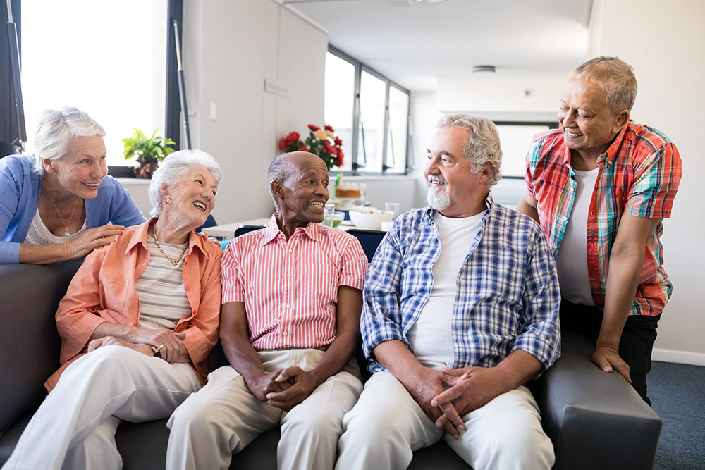 Happy seniors on couch talking in senior living community