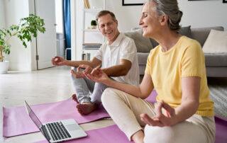 Senior couple sitting on floor in living room meditating during virtual meditation club on laptop