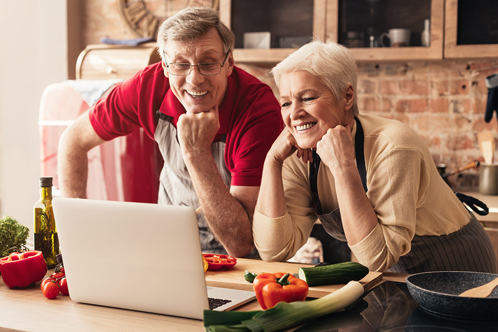 Senior couple in kitchen with laptop in virtual cooking class