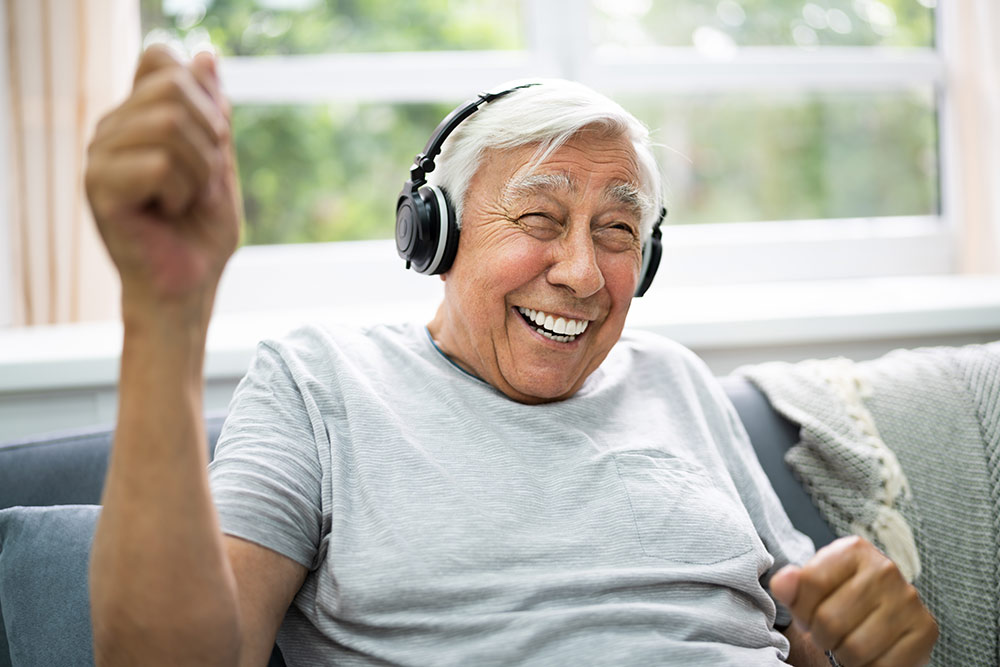 Happy senior man sitting on couch listening to music with headphones on
