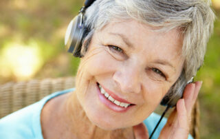 Happy senior woman smiling while listening to music with headphones on