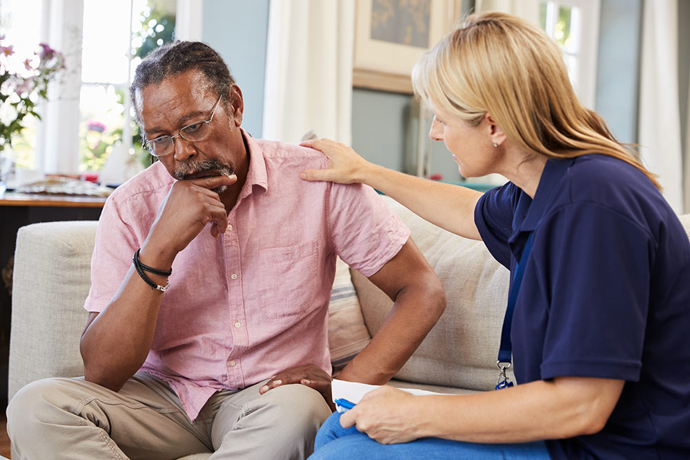 Senior man sitting on couch with caregiver, upset, worried, struggling with mental health issues in senior housing