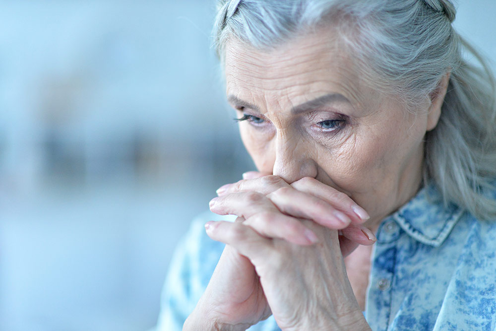 Sad senior woman looking down, holding hands by face