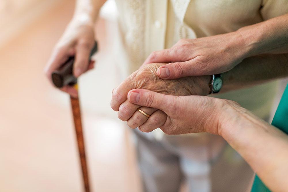 Senior hands holding cane with caregiver holding hand