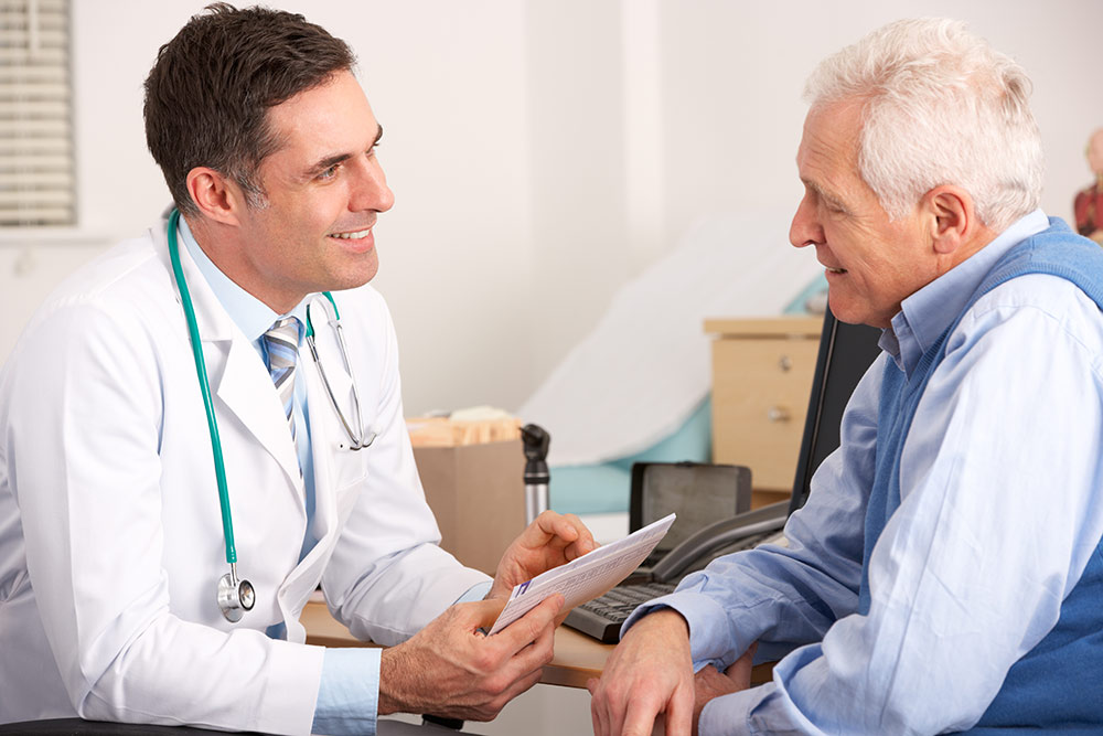 Senior man sitting in doctors office talking with doctor