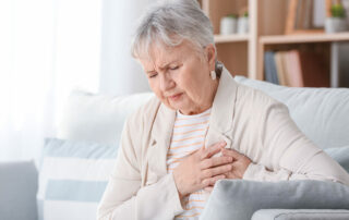 Senior woman sitting on couch, clutching at heart area with worried look
