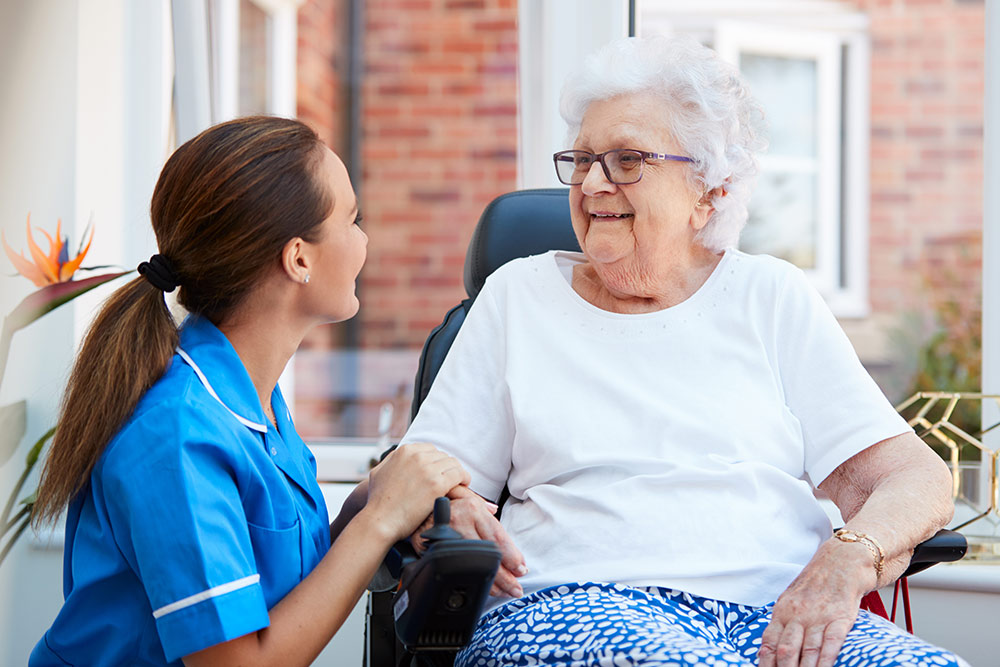 Senior woman sitting down with caregiver in assisted living community