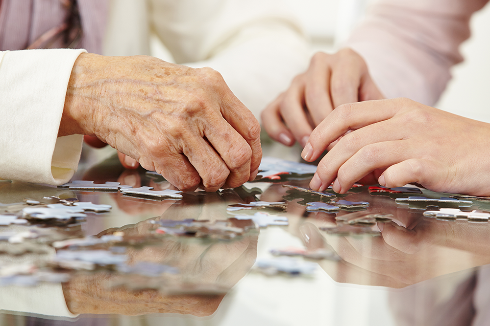 Close up of senior hands with loved one doing a puzzle on a table