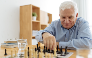 Senior man sitting at a table playing chess