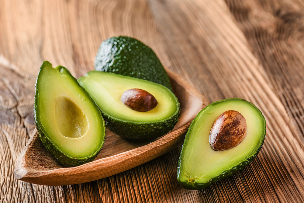 Avocado spread out on table, sliced in half