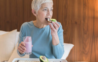 Woman sitting on couch eating avocado toast with a smoothie in the other hand