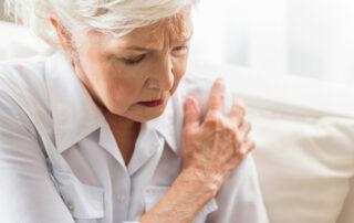 Senior woman holding shoulder, joint pain
