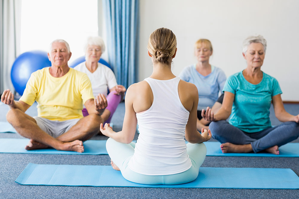 Group of seniors in senior living community meditating