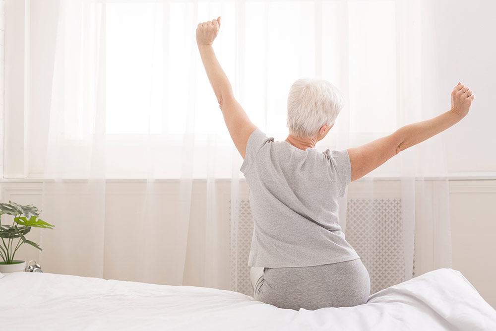 Senior woman sitting up in bed stretching, well rested