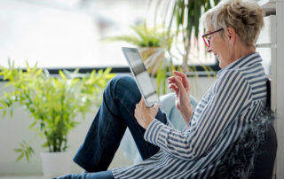 A woman uses her tablet to stay connected to friends and family.